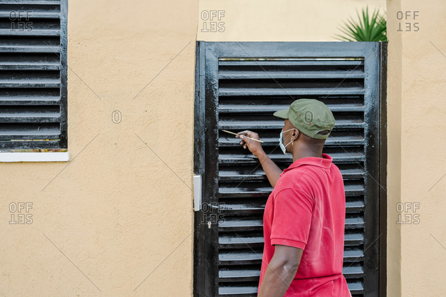 Afro man with mask painting the iron door