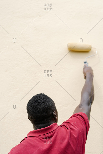 Rear view of a African American man painting a wall with a paint roller