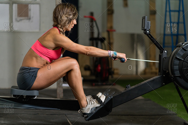 Fitness woman doing a rowing workout in the garage