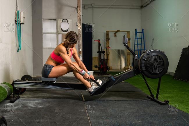 Sportswoman tying her feet to a rowing machine in her garage