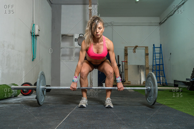 Front view of a fitness woman lifting weight in her garage