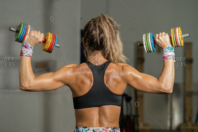 Rear view of a fitness woman lifting colorful dumbbells