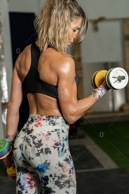 Fitness woman lifting colorful dumbbells