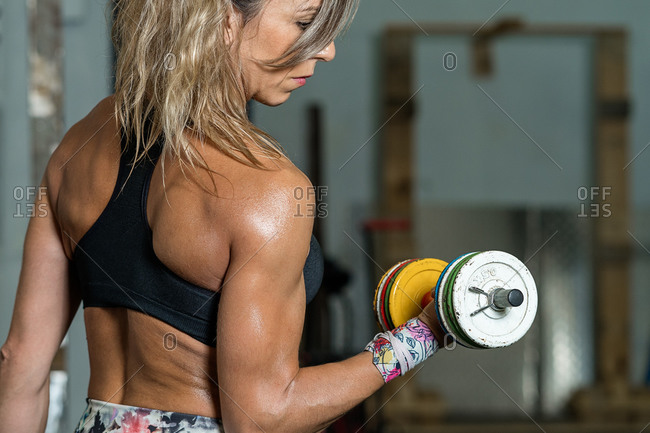 Closeup of a fitness woman lifting colorful dumbbells