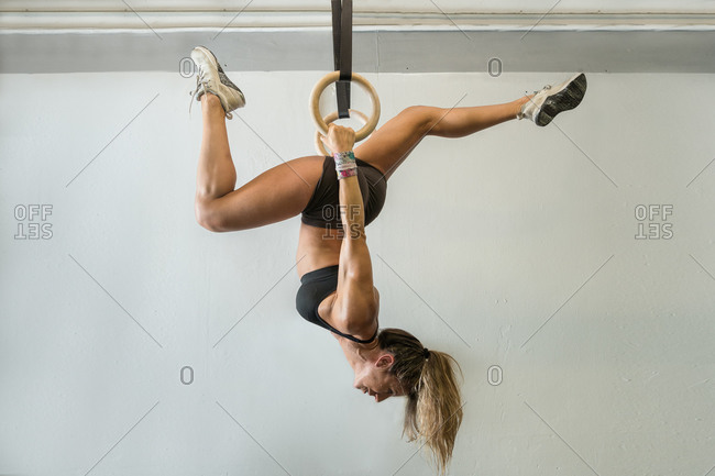 Fitness woman training using gymnastic rings in her garage