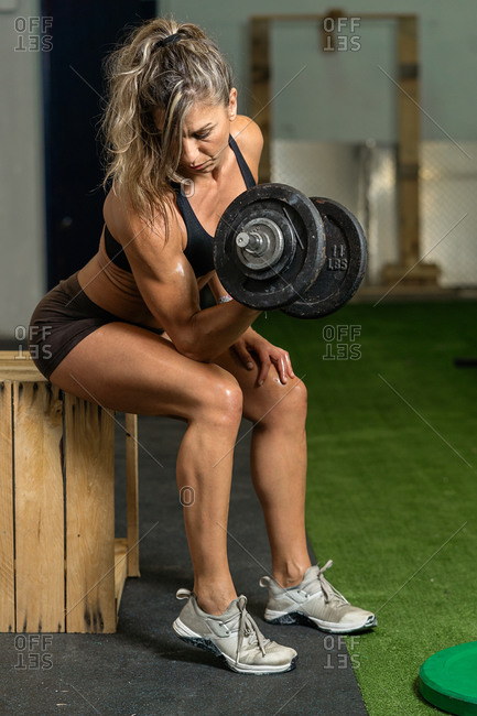 Female athlete training with a dumbbell in the garage