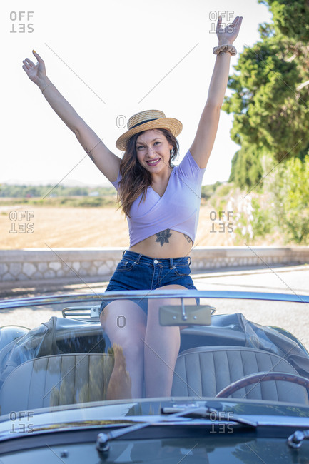 Beautiful and happy woman wearing a hat inside a cabriolet car raising arms and smiling