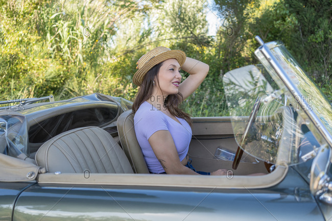 Beautiful and elegant woman wearing hat while driving a cabriolet car