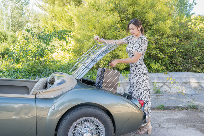 Beautiful and elegant woman putting her shopping bags in her green convertible car parked on the street