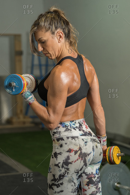 Fitness woman lifting multicolored dumbbells in her garage
