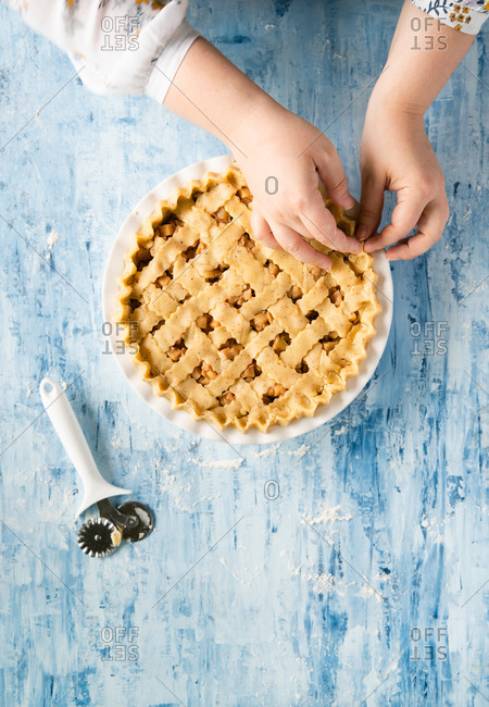 Woman making traditional apple pie from above