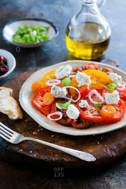 Fresh colorful heirloom tomato salad with ricotta on dark background close up