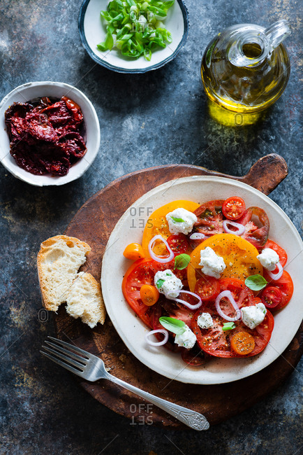 Fresh colorful heirloom tomato salad with ricotta on dark background from above