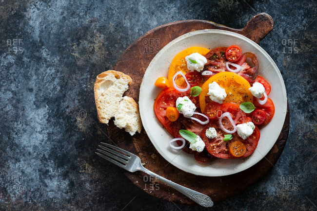 Fresh colorful heirloom tomato salad with ricotta on dark background
