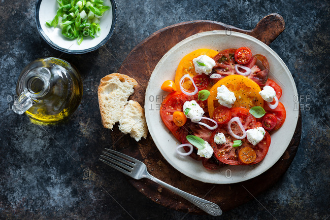 Overhead view of fresh colorful heirloom tomato salad with ricotta on dark background
