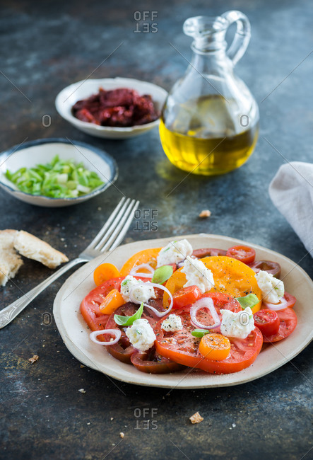 Fresh colorful heirloom tomato salad with olive oil and ricotta cheese