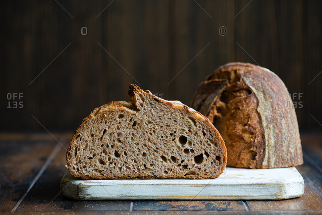 Loaf of homemade whole wheat sourdough bread on a wooden board