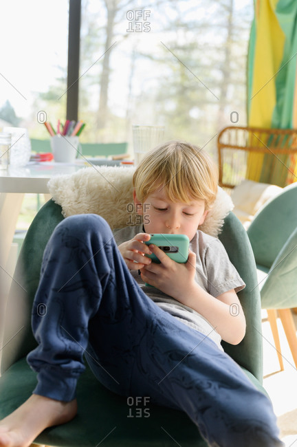 Boy (4-5) sitting in living room with smart phone