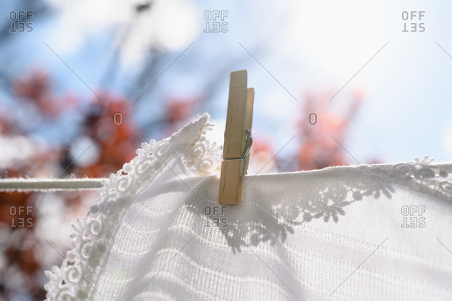 White tablecloth drying on clothesline in sunlight