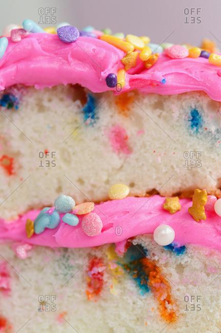 Colorful sprinkles on pink cake frosting