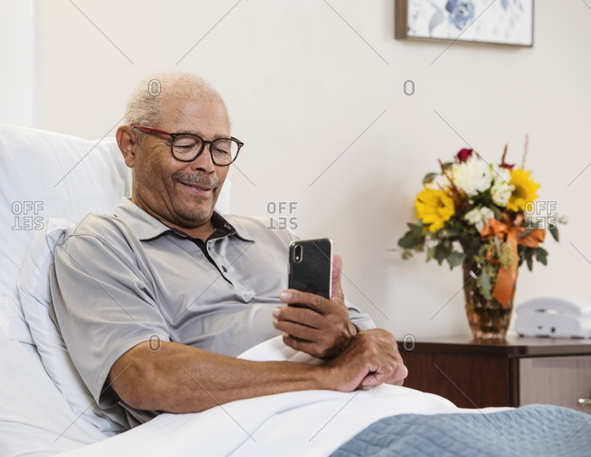 Senior man lying in bed and using smart phone
