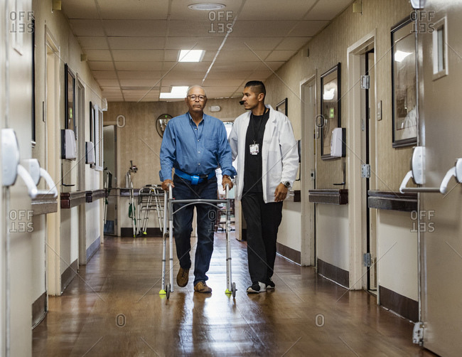 Male nurse assisting senior man walking down corridor with mobility walker