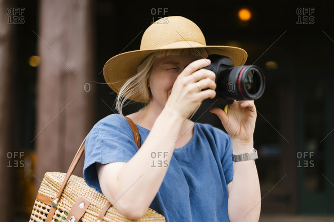 Woman photographing with digital camera�
