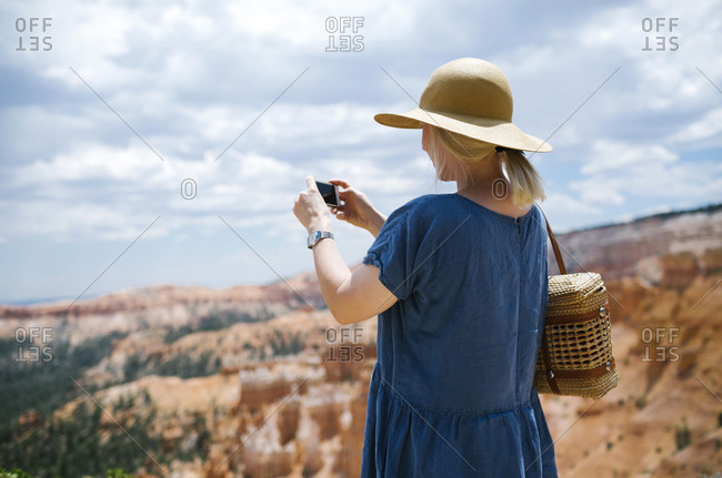 USA, Utah, Bryce Canyon, Woman photographing canyon with smart phone
