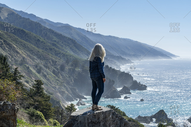 USA, California, Big Sur, Woman standing at the edge of cliff looking at view