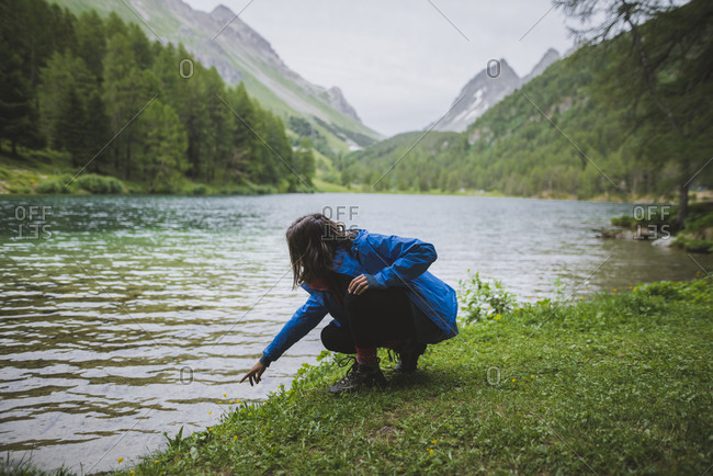 Switzerland, Bravuogn, Palpuognasee, Young woman crouching by�Palpuognasee lake in Swiss Alps
