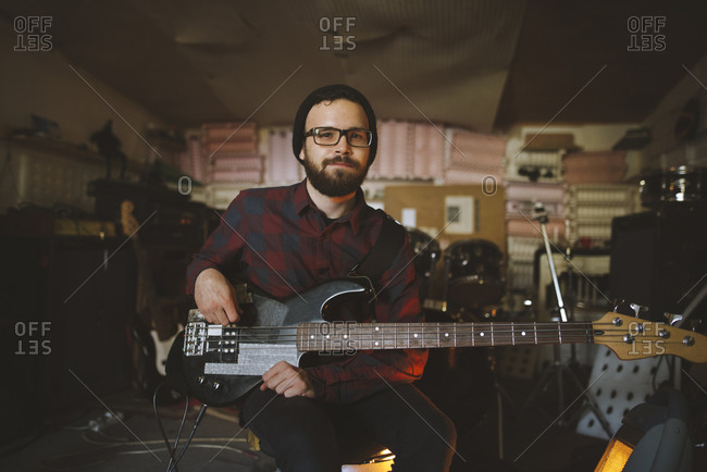 Young man playing bass guitar during rehearsal in garage