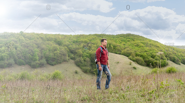 Adult man with backpack climbs the green hills and admires the scenery