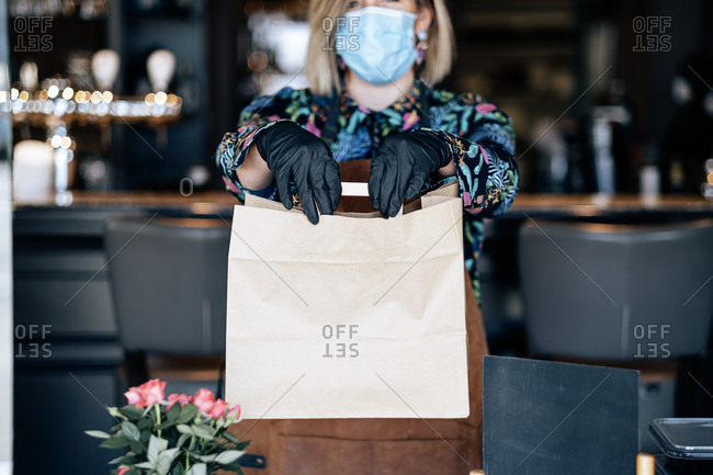 Woman at the restaurant door giving ready food in a paper shopping bag during coronavirus outbreak