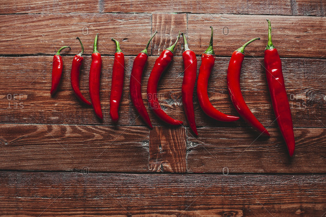 Red hot chili peppers in a white tray on wooden background.