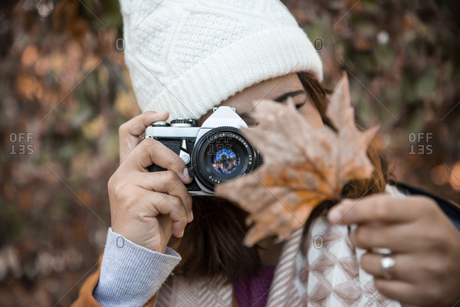 Woman photographing the typical maple leaf in autumn