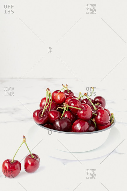 Fresh ripe red cherry with stalks in white ceramic pot placed on marble table against white wall