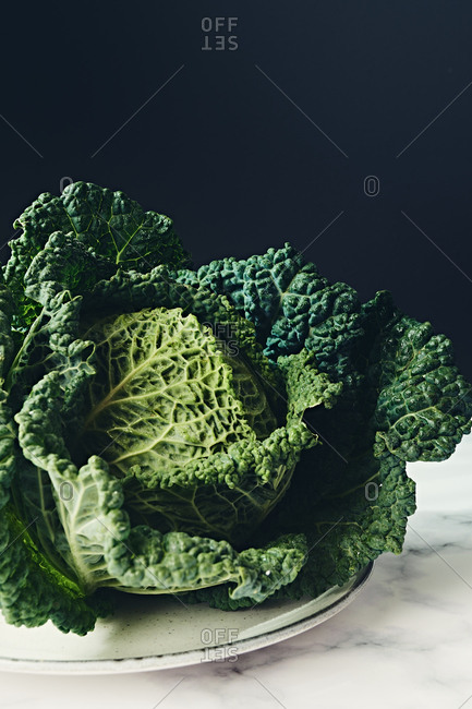 Ripe leafy green savoy cabbage head on marble and dark background
