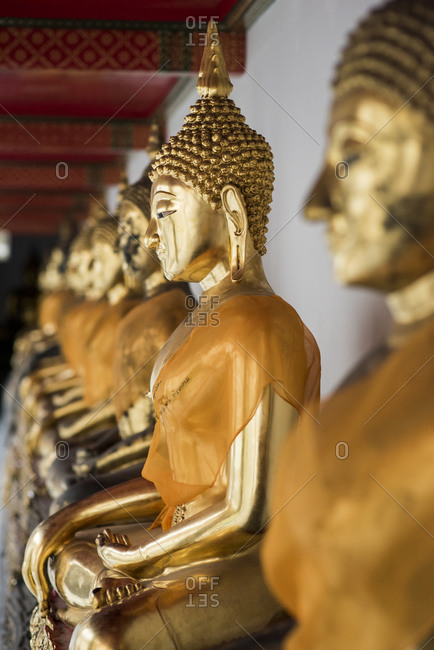 Row of golden Buddha statues at the Wat Pho temple, Bangkok, Thailand.