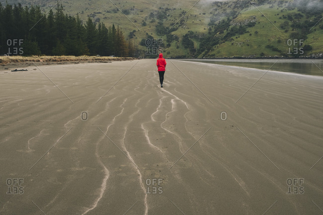 Young woman wearing red jacket at Okains Bay beach, Banks Peninsula
