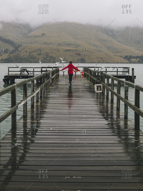Woman on a red jacket happily running at Port Levy Jetty, NZ