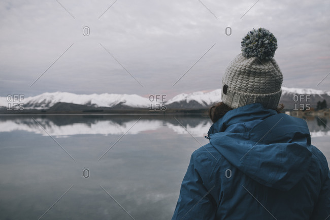 Young woman on a blue jacket stares at Lake Tekapo, Southern Alps