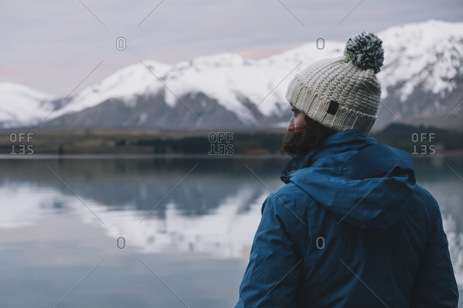 Young woman looking at the southern alps reflection over Lake Tekapo
