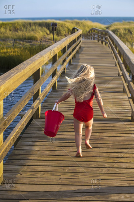 Little Girl From Behind Running On Bridge to Beach with Red Bucket