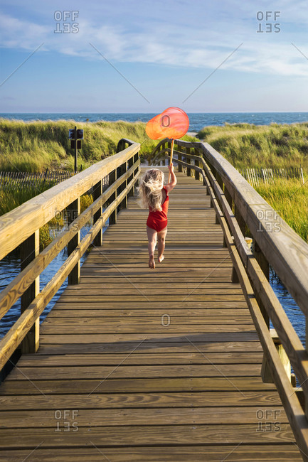 Little Girl from Behind Running On Bridge to Beach with Red Fishing Net