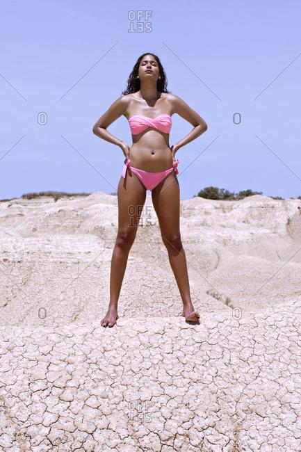 Black model poses on the mud dunes of the Bardenas desert, Spain