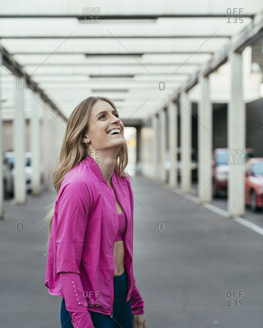 Side view of a happy female runner looking up under a structure