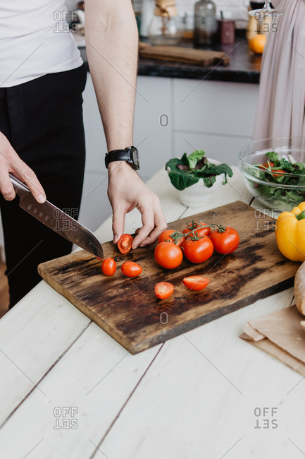 Men's hands cut red tomatoes with a knife on a cutting board