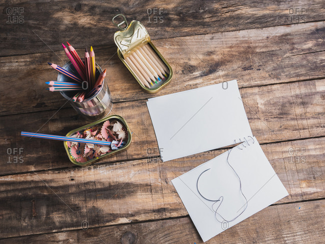 Color pencils on a tin or can, white paper on display on a wooden table, handicraft concept