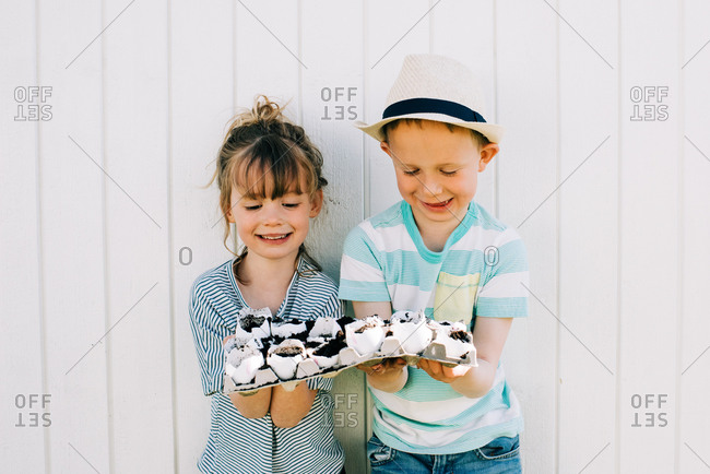 Siblings holding their planted egg shells smiling proudly