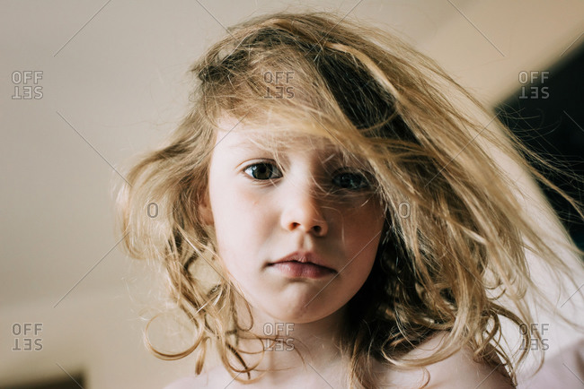 Candid portrait of young girl with bed head hair in the morning
